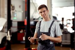 A handsome automechanic is filling in a form concerning the work done royalty free stock image