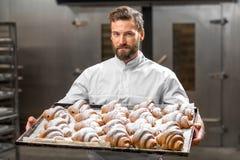 Handsome baker holding tray full of freshly baked croisants Royalty Free Stock Image