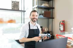 Handsome Baker Smiling While Working In Shop. Portrait of mid adult seller receiving payment through credit card at bakery store royalty free stock image