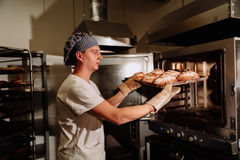Handsome baker in uniform holding tray full of freshly baked bread at the manufacturing royalty free stock photography