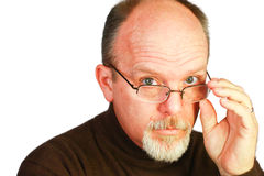Handsome bald man with goatee looking over glasses Stock Photography