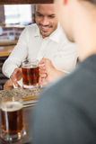 Handsome bar tender giving a pint to customer. In a pub stock image