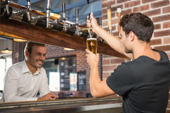 Handsome bar tender pouring a pint for a customer Royalty Free Stock Photography
