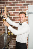 Handsome bar tender pouring a pint Royalty Free Stock Image