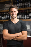Handsome bar tender standing behind his counter Royalty Free Stock Photos