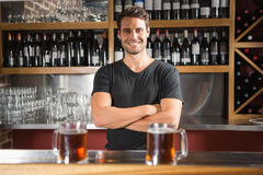 Handsome bar tender standing behind his counter Stock Photography