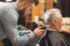 Handsome barber designing haircut of the aging man in barbershop. Full of concentration. Involved masterful creative barber standing in the barbershop and stock photos