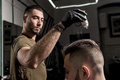 Handsome barber is fixing the styling of brutal young bearded man with a dry styler at a barbershop stock images