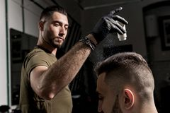 Handsome barber is fixing the styling of brutal young bearded man with a dry styler at a barbershop stock photo