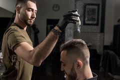 Handsome barber is fixing the styling of brutal young man with a dry styler at a barbershop stock images