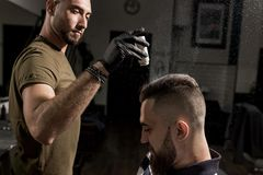 Handsome barber is fixing the styling of brutal young man with a dry styler at a barbershop stock image