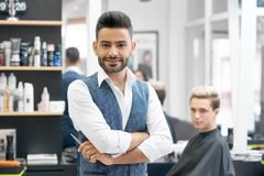 Handsome barber posing standing in front of young client sitting near mirror. royalty free stock photography