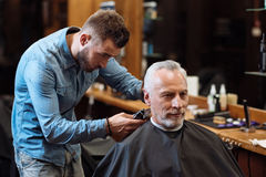 Handsome barber trimming hair of old man. Perfect trim. Youthful attractive hairstylist standing and accurately trimming hair of old client at barbershop Royalty Free Stock Photos
