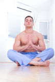 Handsome bare chested man doing yoga. Good looking young handsome bare chested man doing yoga at his home indoors royalty free stock photography