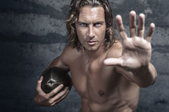 Handsome bare chested muscle model. Is opening his hand in halt gesture and holds football ball Stock Images