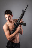 Handsome bare-chested soldier is holding a rifle Stock Photography
