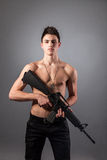 Handsome bare-chested soldier is holding a rifle Royalty Free Stock Photos