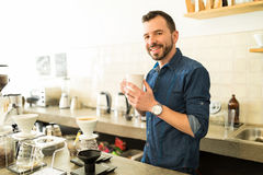 Handsome barista with a cup of coffee. Portrait of a Hispanic male barista holding a cup of coffee and smiling in a coffee shop Stock Photography