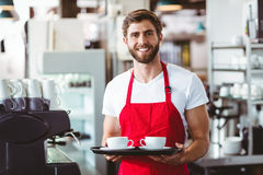 Handsome barista holding two cups of coffee Stock Photos