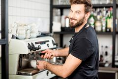 Barista making coffee. Handsome barista making coffee with coffee machine at the bar of the modern cafe Stock Photography