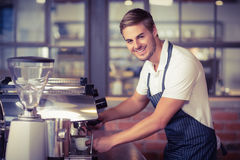 Handsome barista making a cup of coffee. Portrait of a handsome barista making a cup of coffee at the coffee shop Stock Images