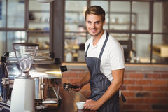 Handsome barista making a cup of coffee. Portrait of a barista making a cup of coffee at the coffee shop Stock Photo