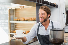 Handsome barista offering a cup of coffee Stock Photography