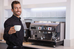 Handsome barista offering a cup of coffee to camera Stock Photos