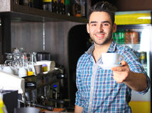 Handsome barista offering a cup of coffee Stock Photos