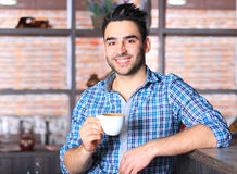 Handsome barista offering a cup of coffee Stock Images