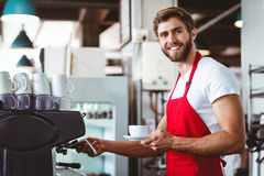 Handsome barista preparing a cup of coffee. With the coffee machine Royalty Free Stock Image