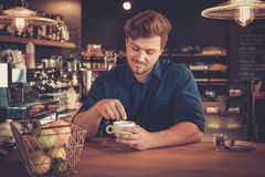 Handsome barista tasting a new type of coffee in his coffee shop Stock Photography