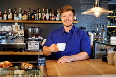 Handsome barista tasting a new type of coffee in his coffee shop Royalty Free Stock Images