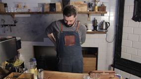 Barista wears an apron before starting work in coffee house. A bearded man is dressing in a protective uniform. stock footage