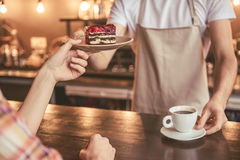 Handsome barista working. Cropped image of handsome barista in apron giving a cake and coffee to girl while working at the bar counter in cafe Stock Images