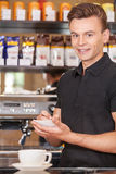 Handsome barista writing check and smiling. Stock Photo
