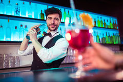 Handsome barkeeper preparing cocktail at bar counter. Portrait of confident handsome barkeeper preparing cocktail at bar counter royalty free stock images