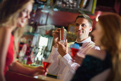 Handsome barman chatting to customers stock images