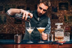 Handsome Barman creating professional cocktails. Details of alcoholic drinks and beverages at pub or bar stock images