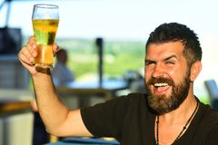 Handsome barman holding a pint of beer. Man holds glass of beer. Enjoy in pub. Beer time. stock photography