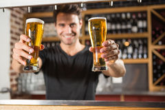 Handsome barman holding a pint of beer. In a pub stock photos