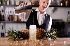 A handsome barman and a Pina Colada coctail. A handsome barman is pouring alcohol into a Pina Colada coctail, made of ripe pineapples stock photography