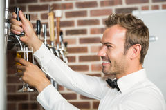 Handsome barman pouring a pint of beer. In a pub stock photography