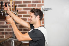 Handsome barman pouring a pint of beer. In a pub stock photos