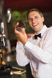 Handsome barman smiling at camera making a cocktail Royalty Free Stock Photo
