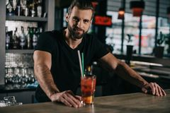 handsome barman standing with alcohol drink royalty free stock images