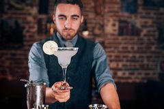 Professional bartender, barman serving fresh made alcoholic beverage, margarita cocktail. Handsome bartender, barman serving fresh made alcoholic beverage Stock Images