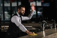 handsome bartender cleaning bar counter and waving hand stock photos