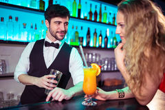 Handsome bartender flirting with young woman Royalty Free Stock Images