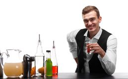 A handsome bartender holds a shot, oranges, bottles of beverages on a white background. stock photo